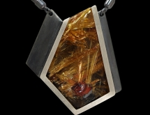 Pendant featuring rutilated quartz with red hematite inclusion in argentium silver, by Wolfgang Vaatz.