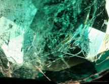 Orange and bluish flash effect in natural Colombian emerald treated with artificial resin fracture filling